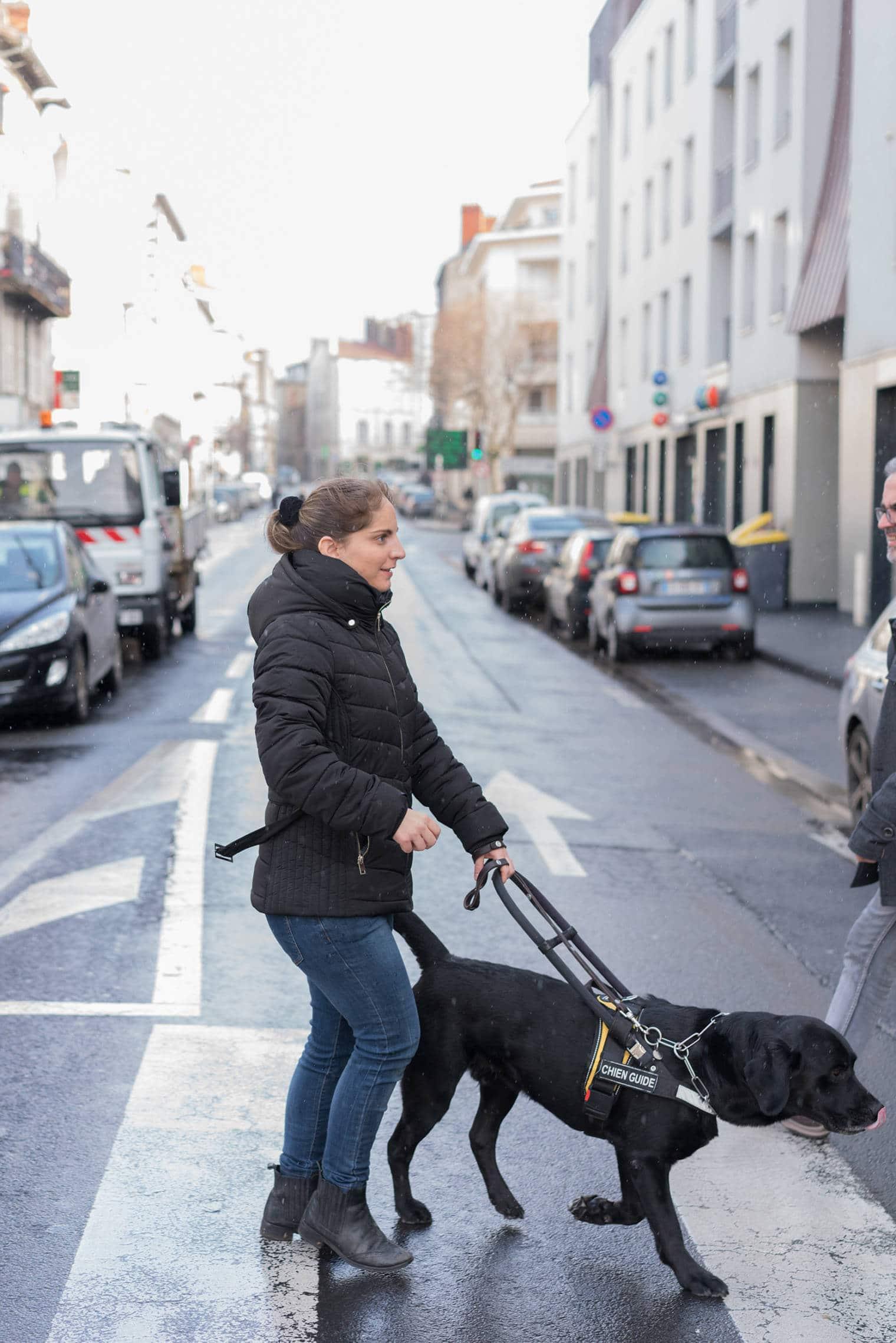 Sabrina Podechard traverse la route au niveau d'un passage piéton avec son chien guide, un labrador noir.