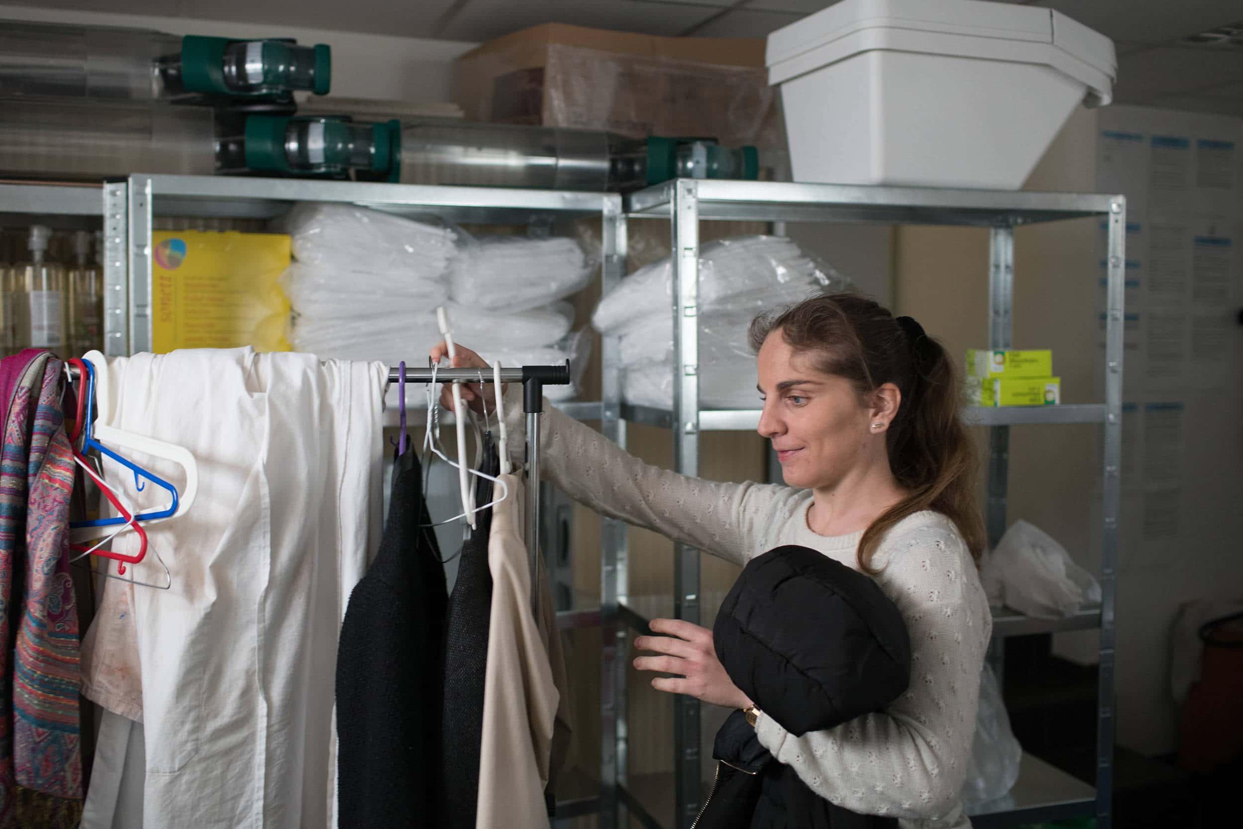 Sabrina accroche son manteau noir au vestiaire en arrivant au travail. Au second plan sont visibles des blouses de travail et différents récipients.