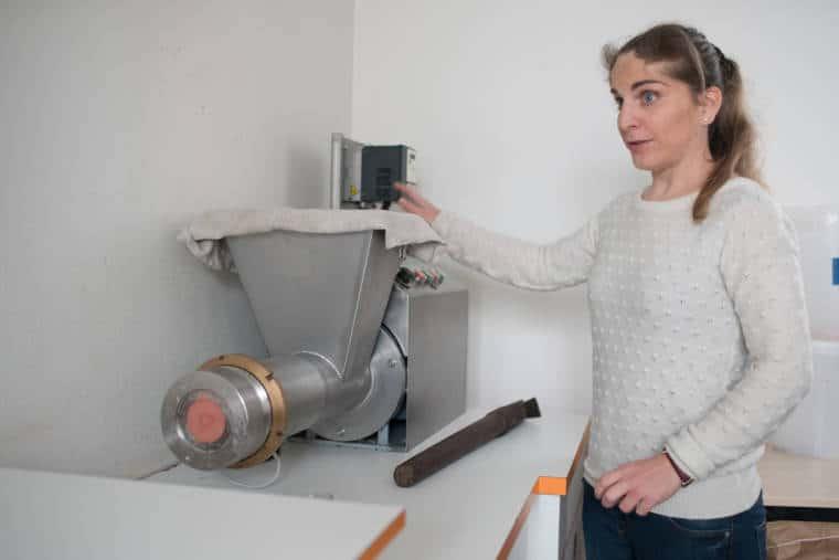 Sabrina désigne une machine en métal située à son côté, contribuant à la conception des savons.