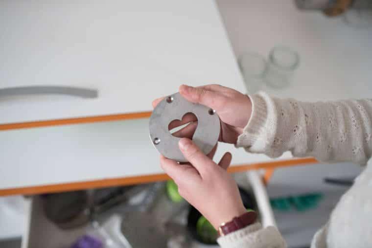 Deux mains sont refermées sur un cylindre métallique s'apparentant à un moule. Une forme de cœur est découpée en son centre.