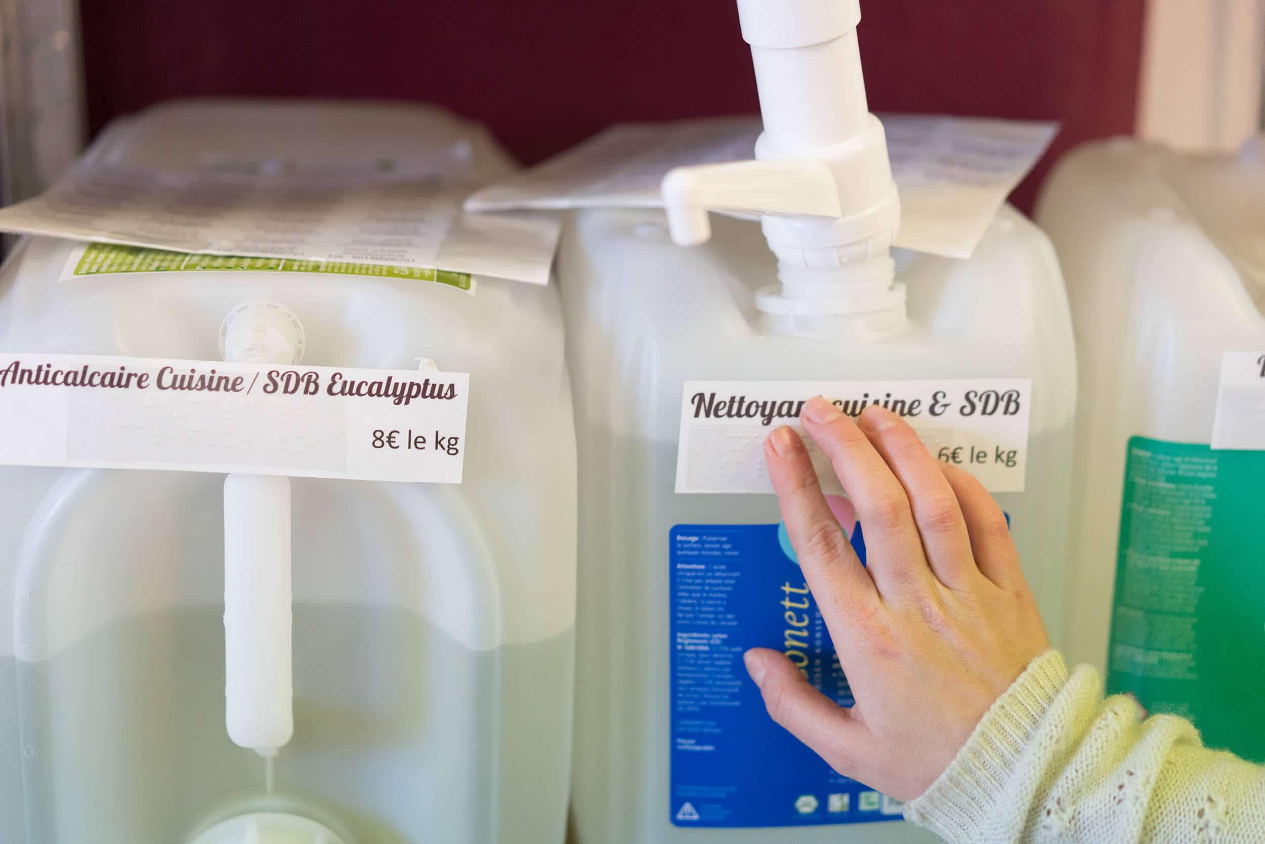 Une main passe sur l'écriture en braille de l'étiquette d'un grand récipient à savon liquide.