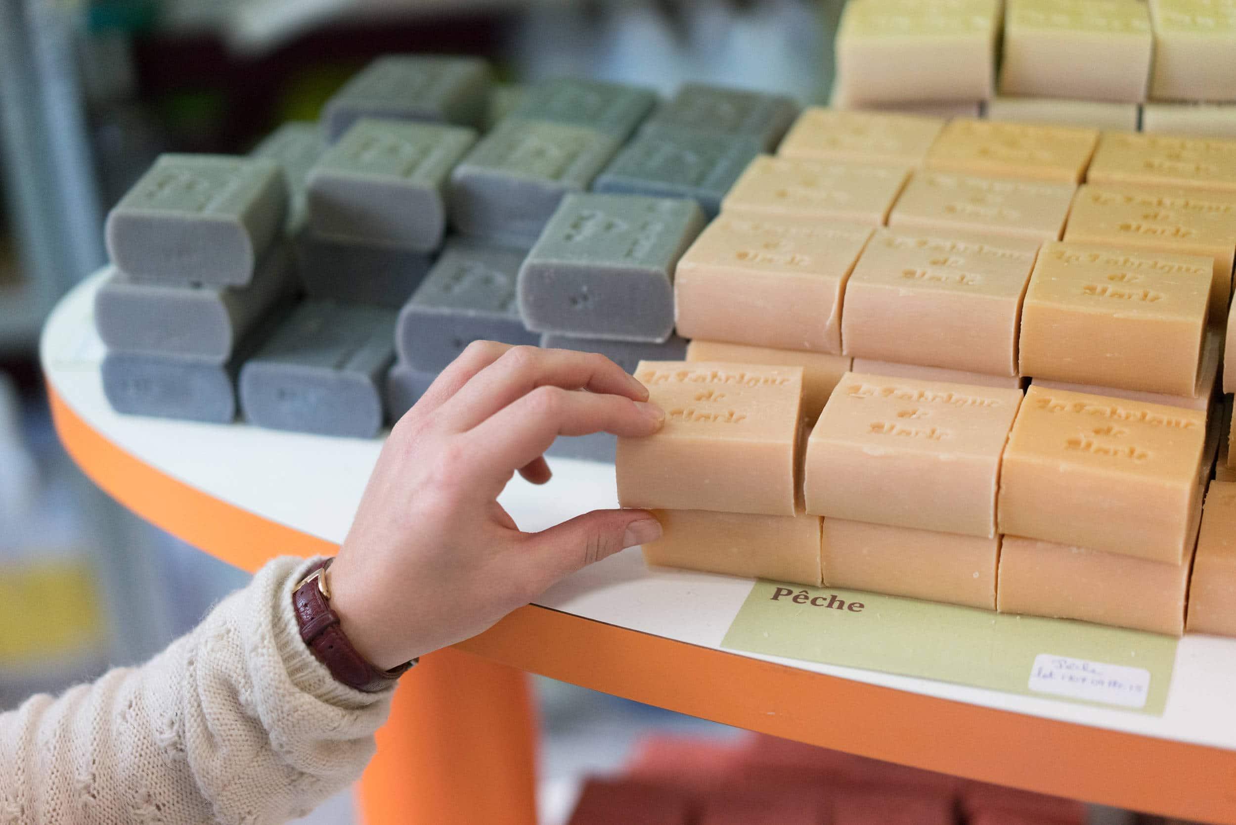 Deux piles de savons rectangulaires respectivement de couleur gris foncé et orange pastel sont posés sur une étagère. Une main se saisit de l'un d'eux.