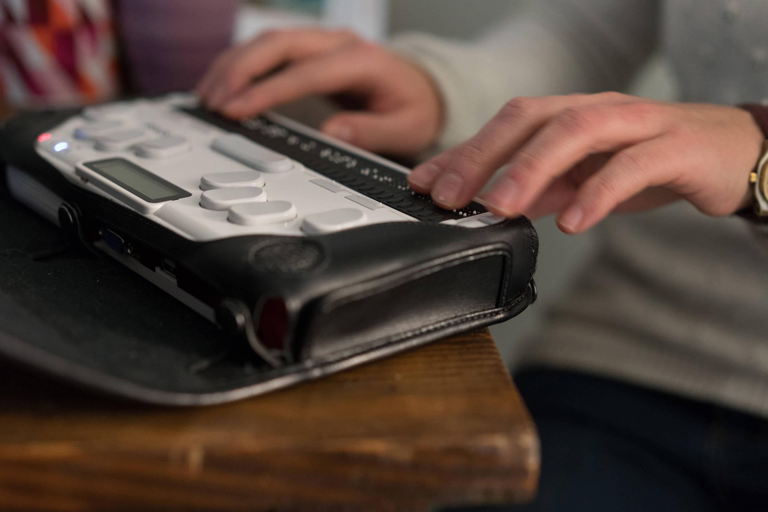Deux mains décryptent un texte restitué en braille sur un appareil portatif.