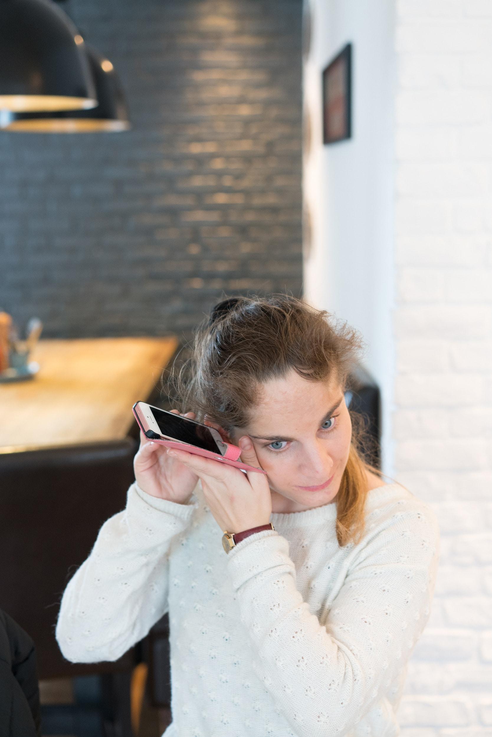 Les deux mains de Sabrina portent son téléphone portable à hauteur d'oreille afin d'écouter une transcription.