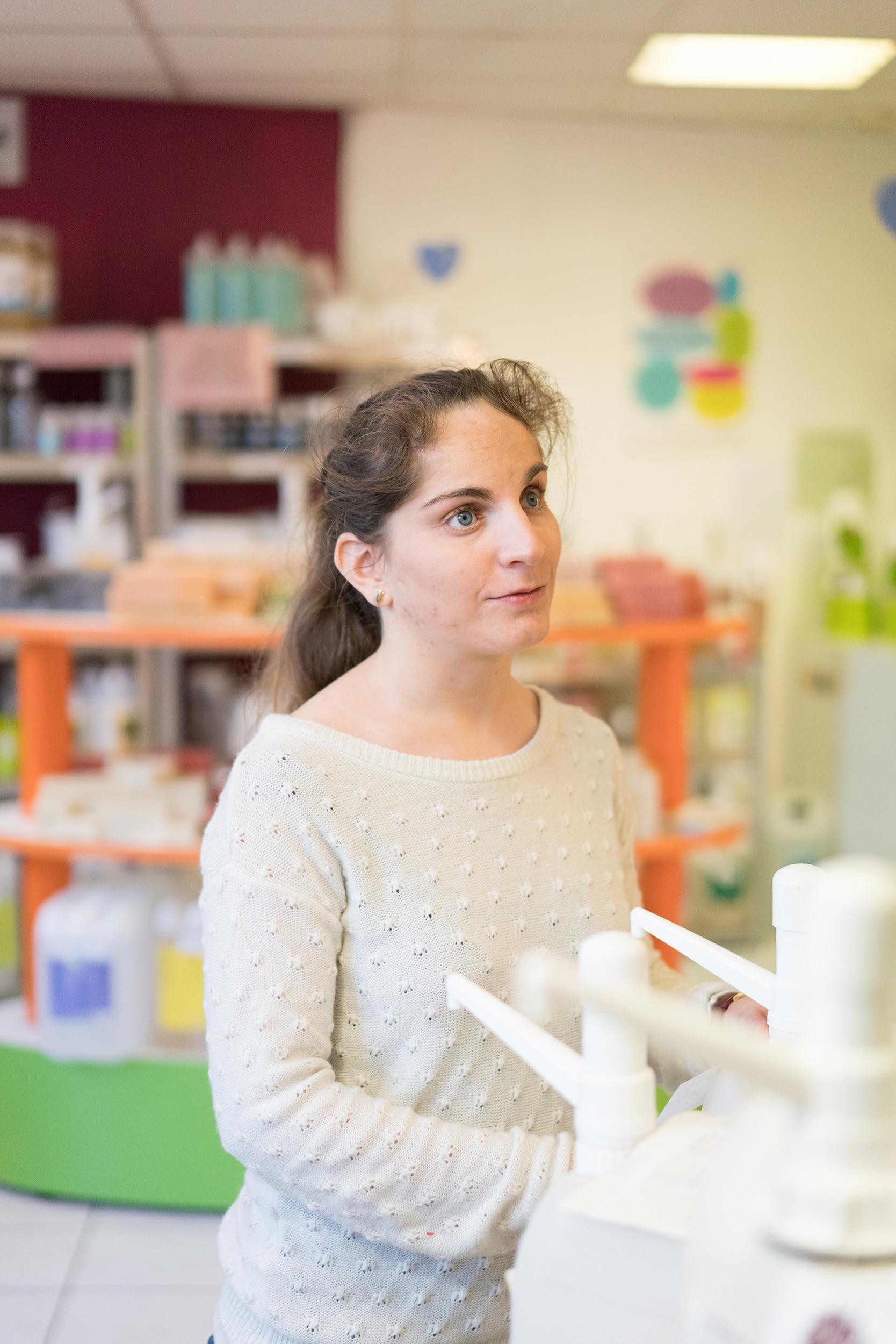 Portrait de Sabrina au premier plan. Au second plan on peut apercevoir le magasin de vente de savons.