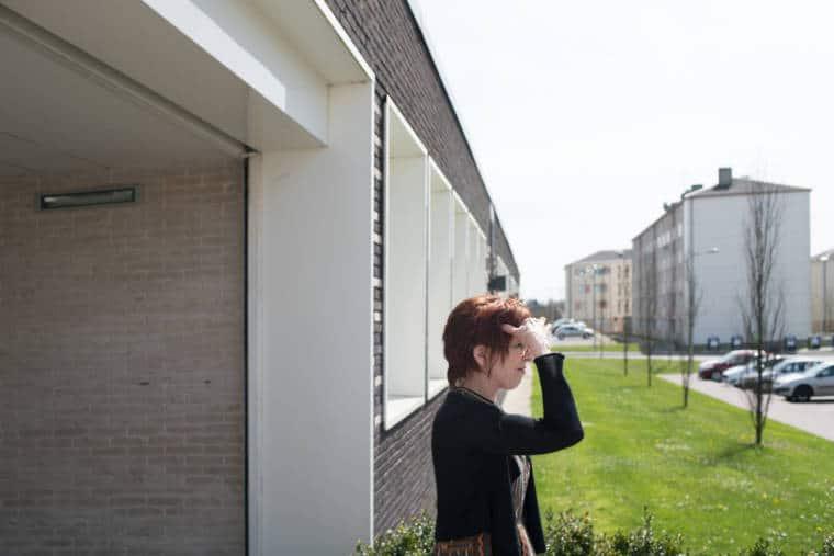 Isabelle, à l'extérieur du bâtiment, regarde au loin en mettant sa main en visière pour se protéger du soleil