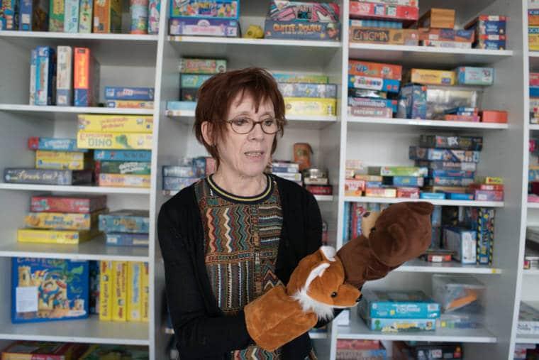 Devant une ludothèque remplie de jeux de société, Isabelle montre deux marionnettes d'ours et de renard qu'elle a enfilées sur ses mains