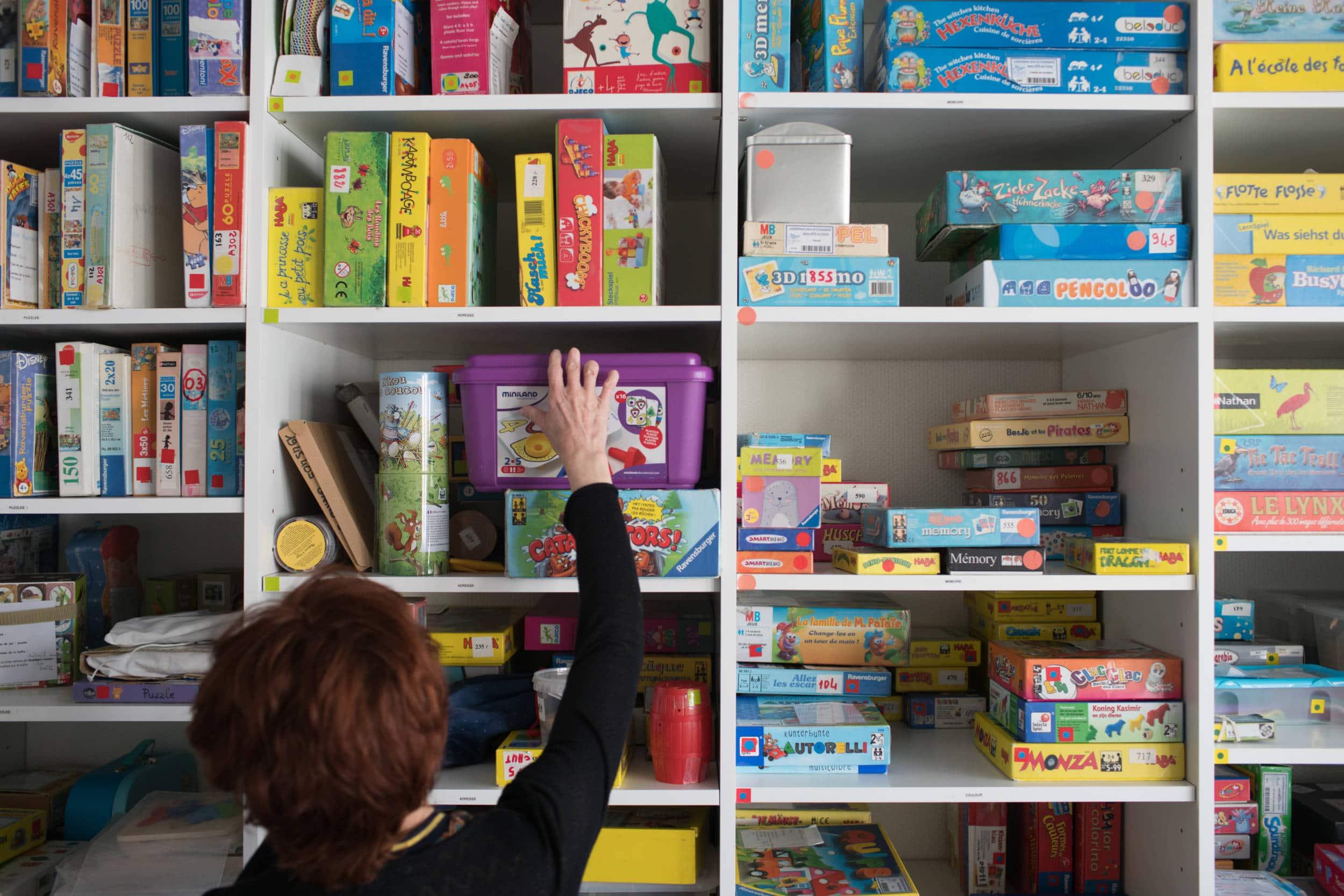 Isabelle se saisit d'une boîte parmi les jeux rangés dans la ludothèque