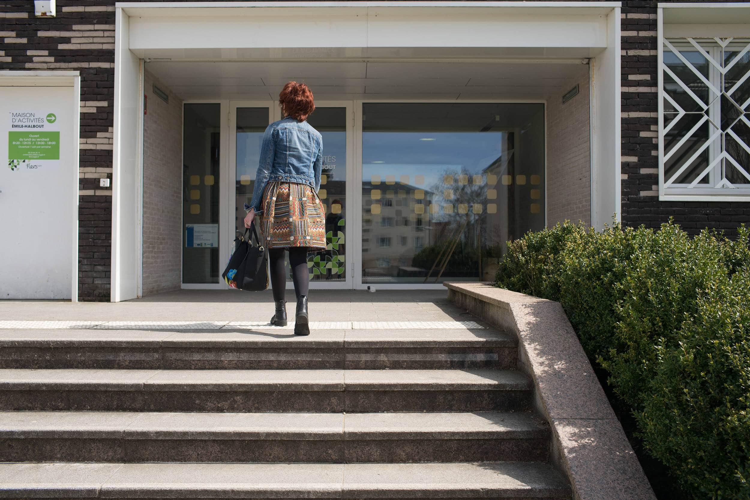 Montant les quelques marches extérieures de la maison d'activités Émile-Halbout