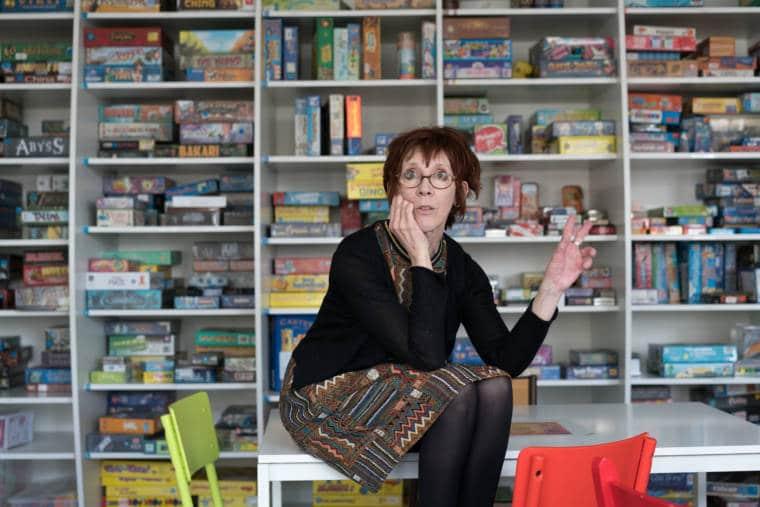 Devant la ludothèque, Isabelle est assise sur un bureau et s'adresse à un auditoire invisible, de face
