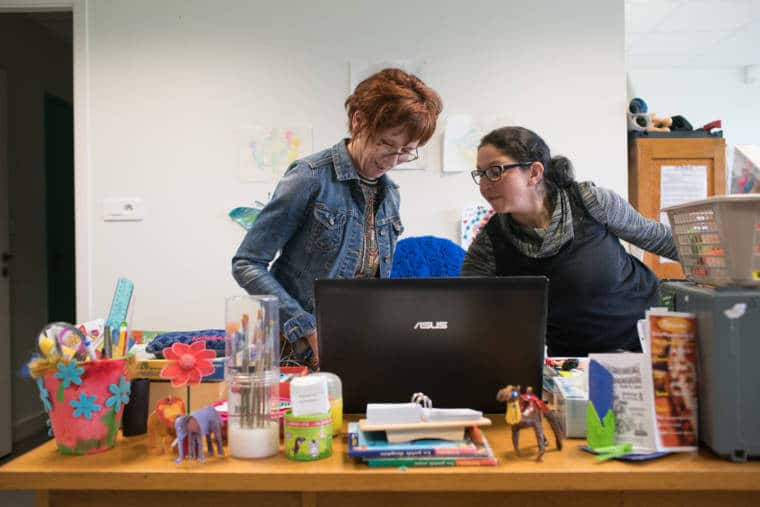 Derrière un ordinateur portable, sur un bureau orné de décorations dans le thème de l'enfance, Isabelle et une collègue, souriantes, travaillent