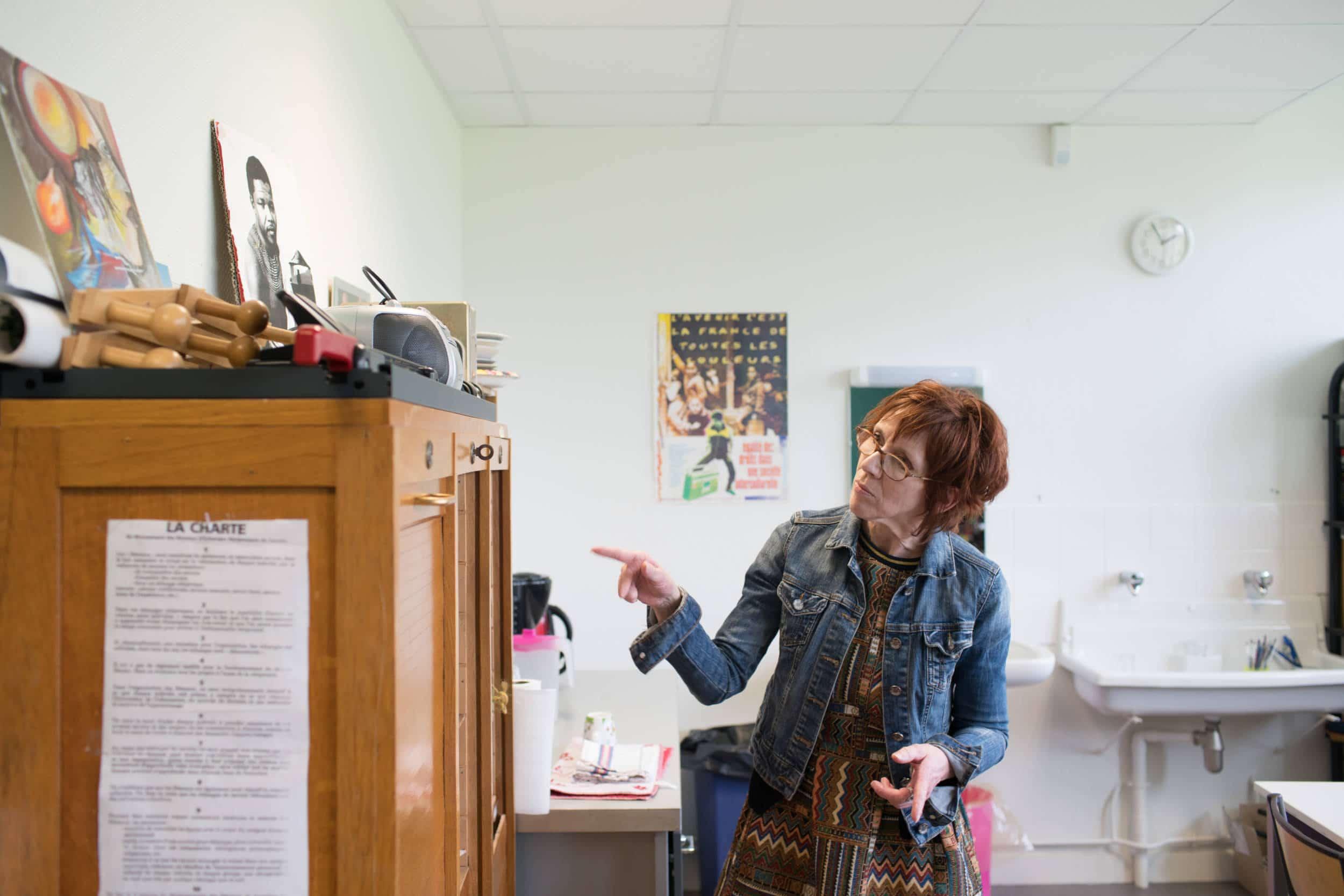 Isabelle désigne une armoire dans son espace de travail