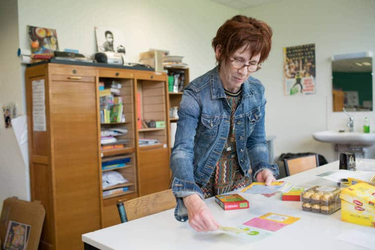 Isabelle dispose des cartes de jeux et d'apprentissage sur un bureau