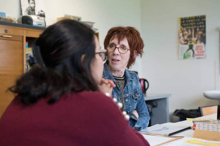 Isabelle converse avec une collègue autour d'une table