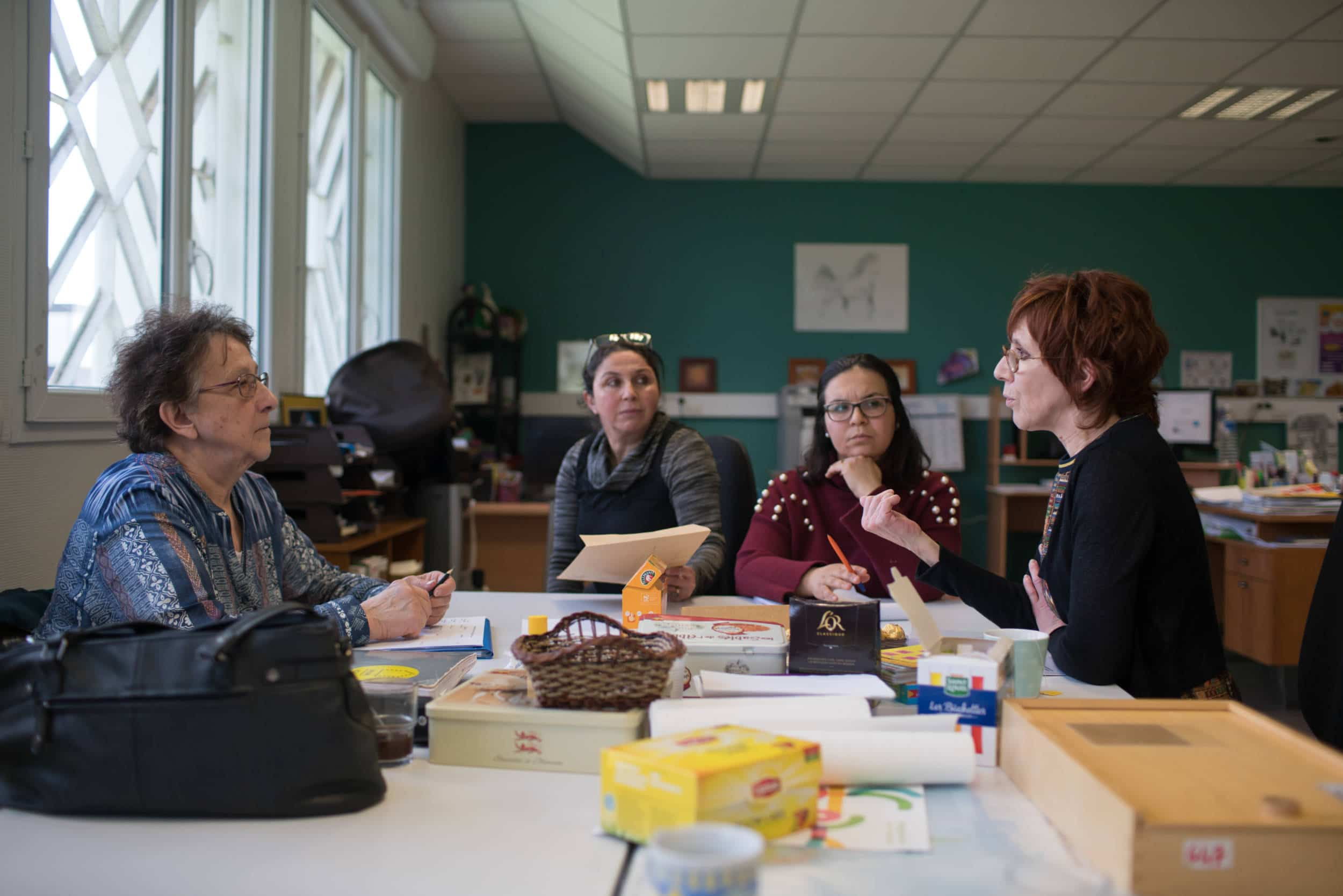 Lors d'une réunion autour d'une table, Iabelle s'adresse à trois de ses collègues de travail