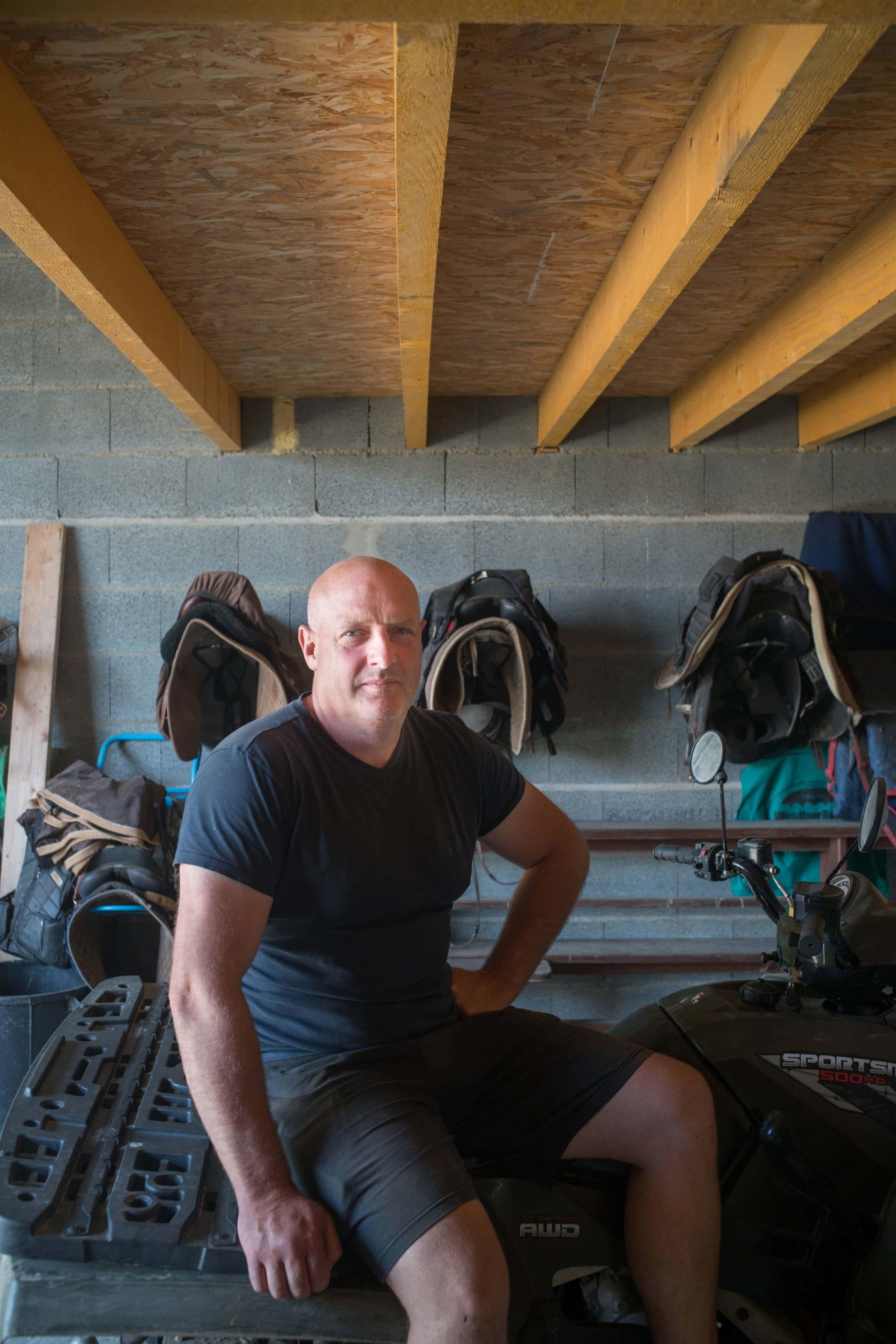David Giraudeau est assis sur son quad. À l'arrière plan des selles sont suspendues.