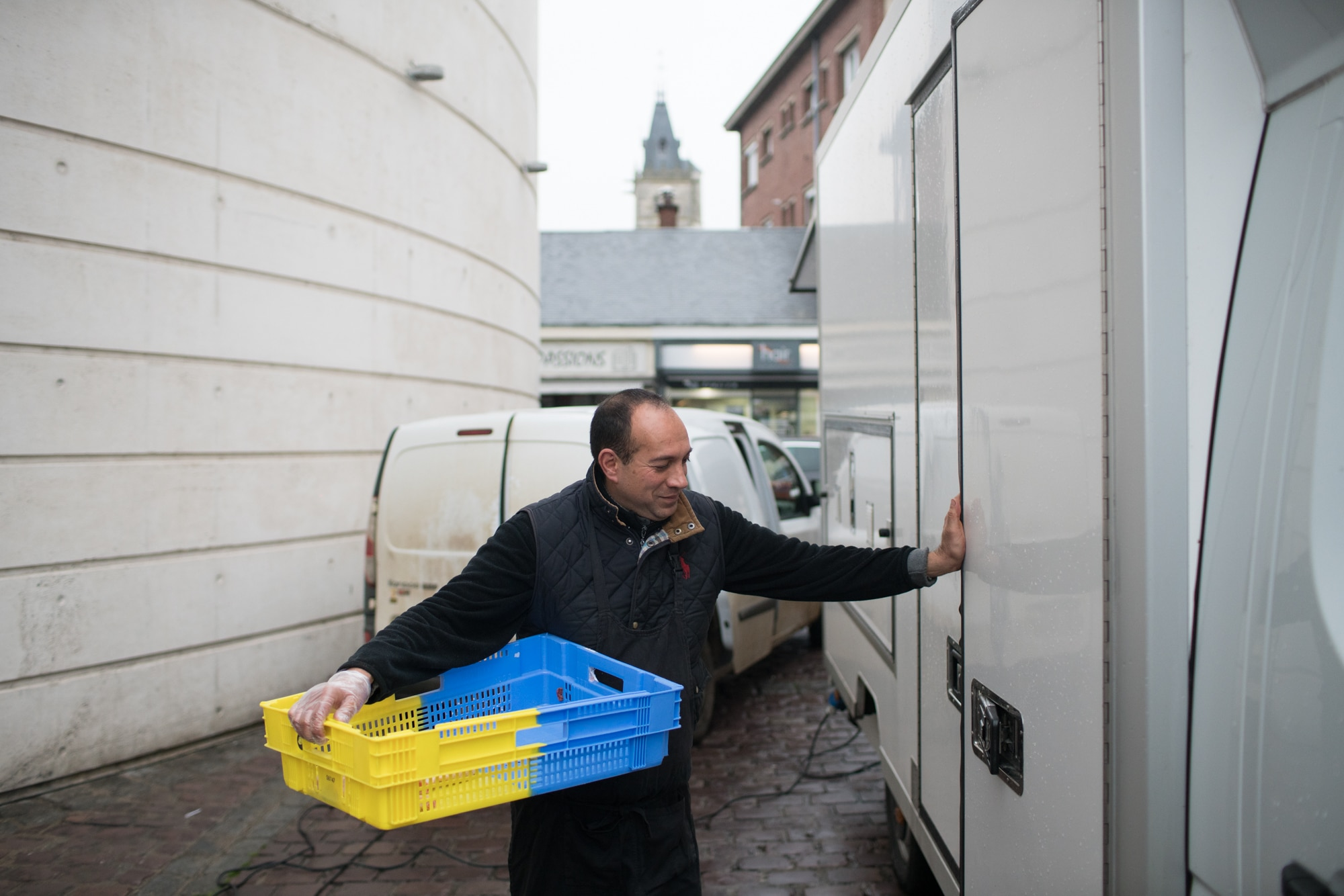 Alain ferme la porte de son camion de la main gauche. Sa main droite, gantée, porte une caisse vide.