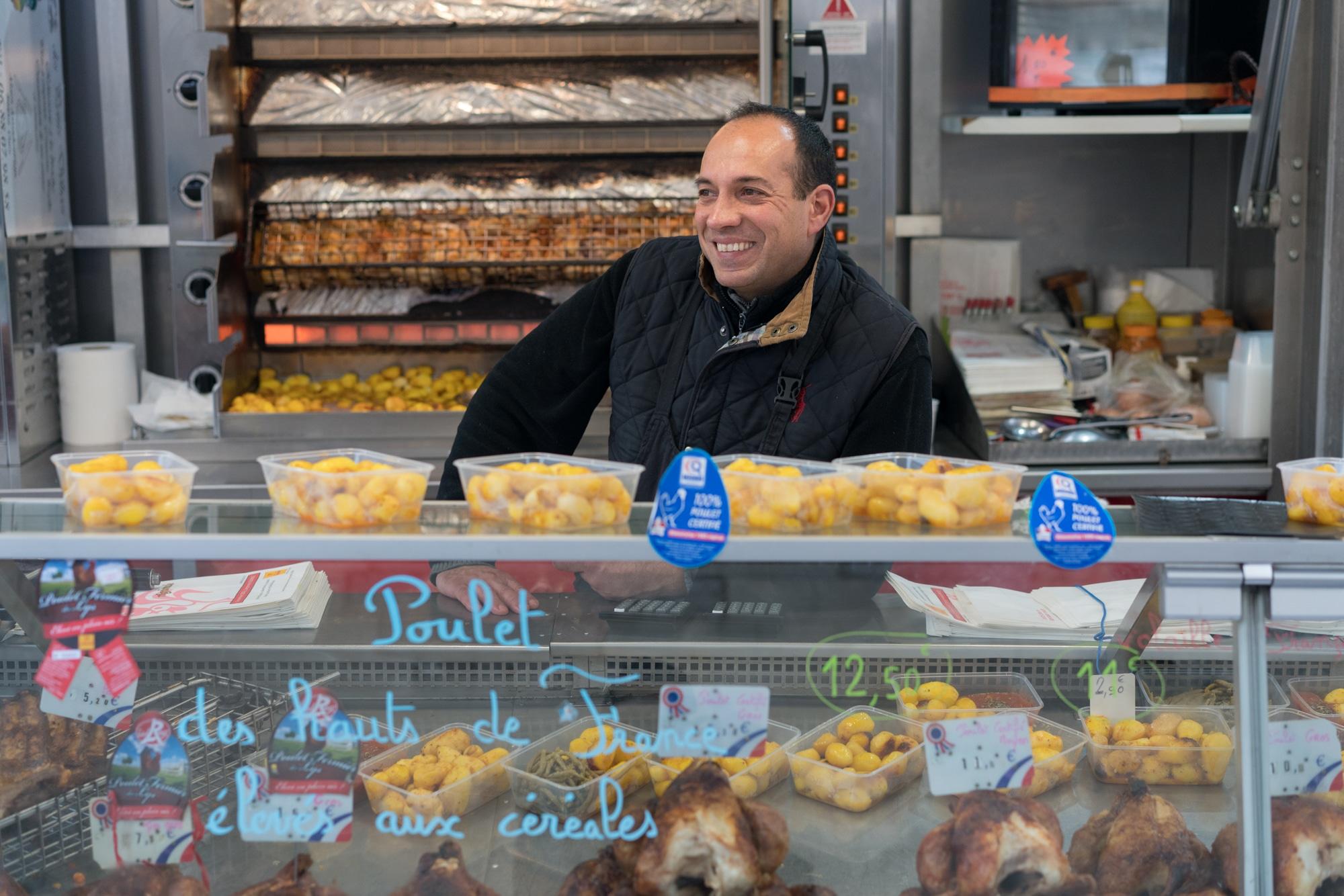 Alain, souriant, se tient dans son camion. Dans la vitrine devant lui on aperçoit des poulets et des pommes de terre.