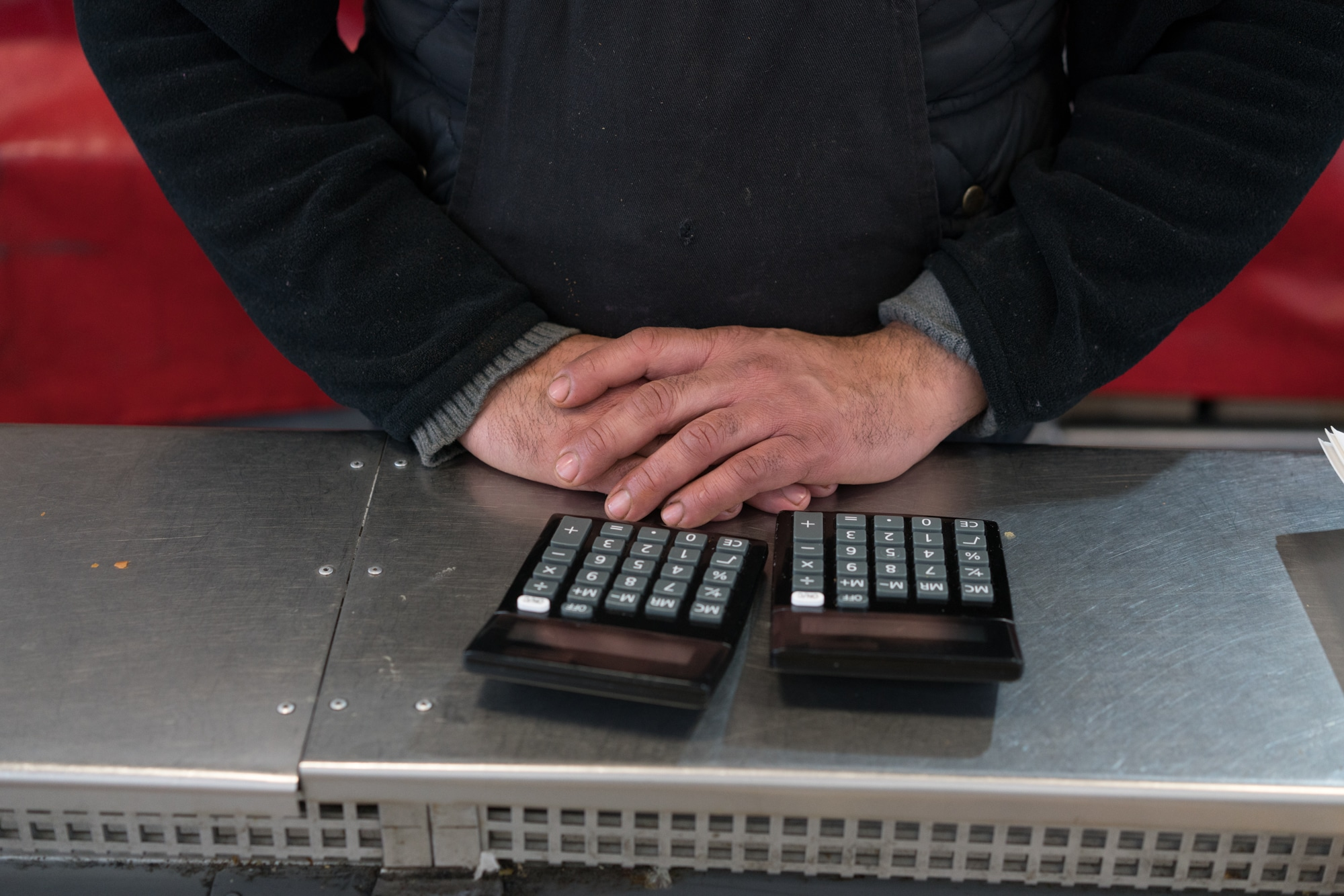 Les mains d'Alain sont jointes devant deux calculatrices.