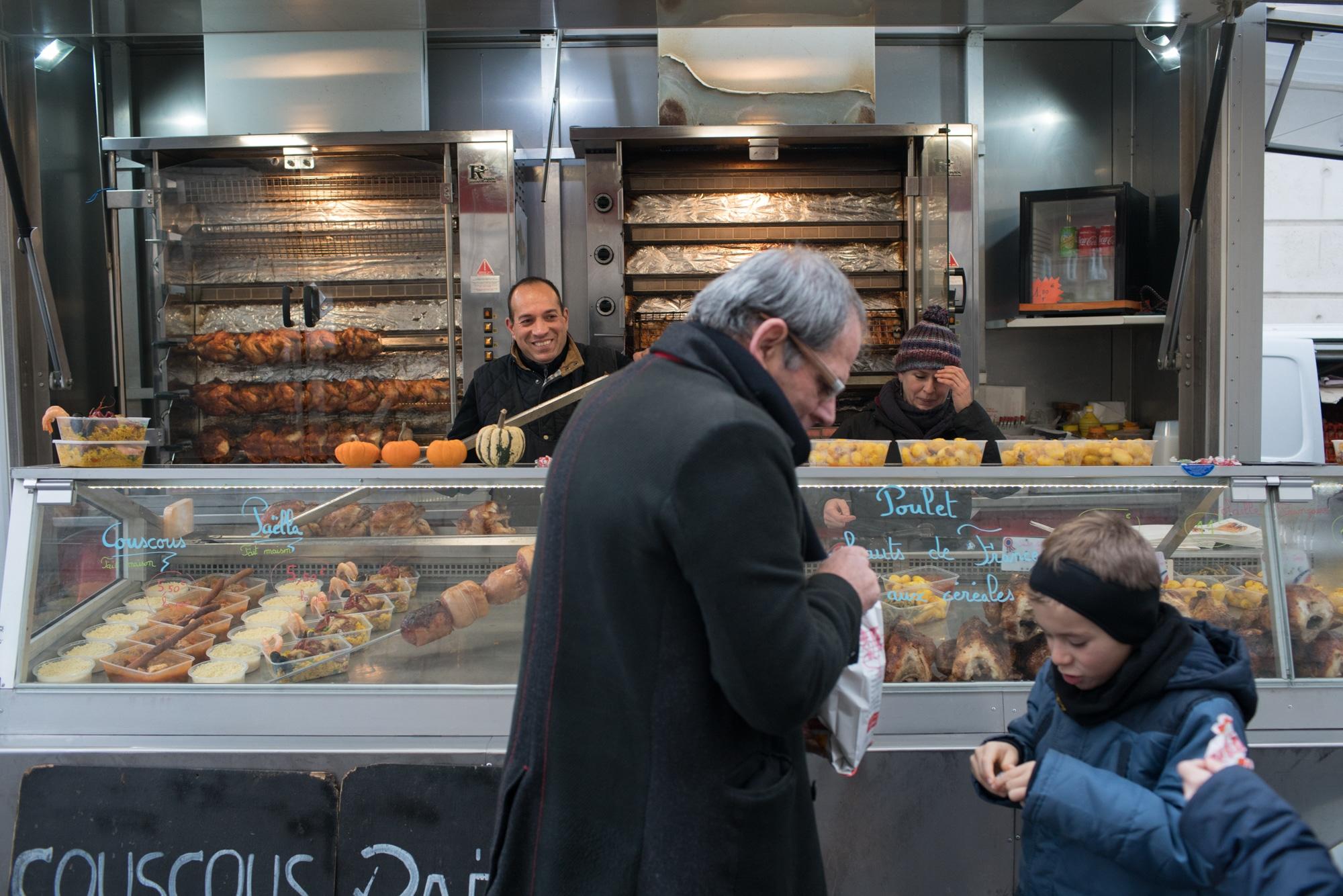 Alain, souriant, observe une homme et un enfant discuter autour d'un poulet rôti.