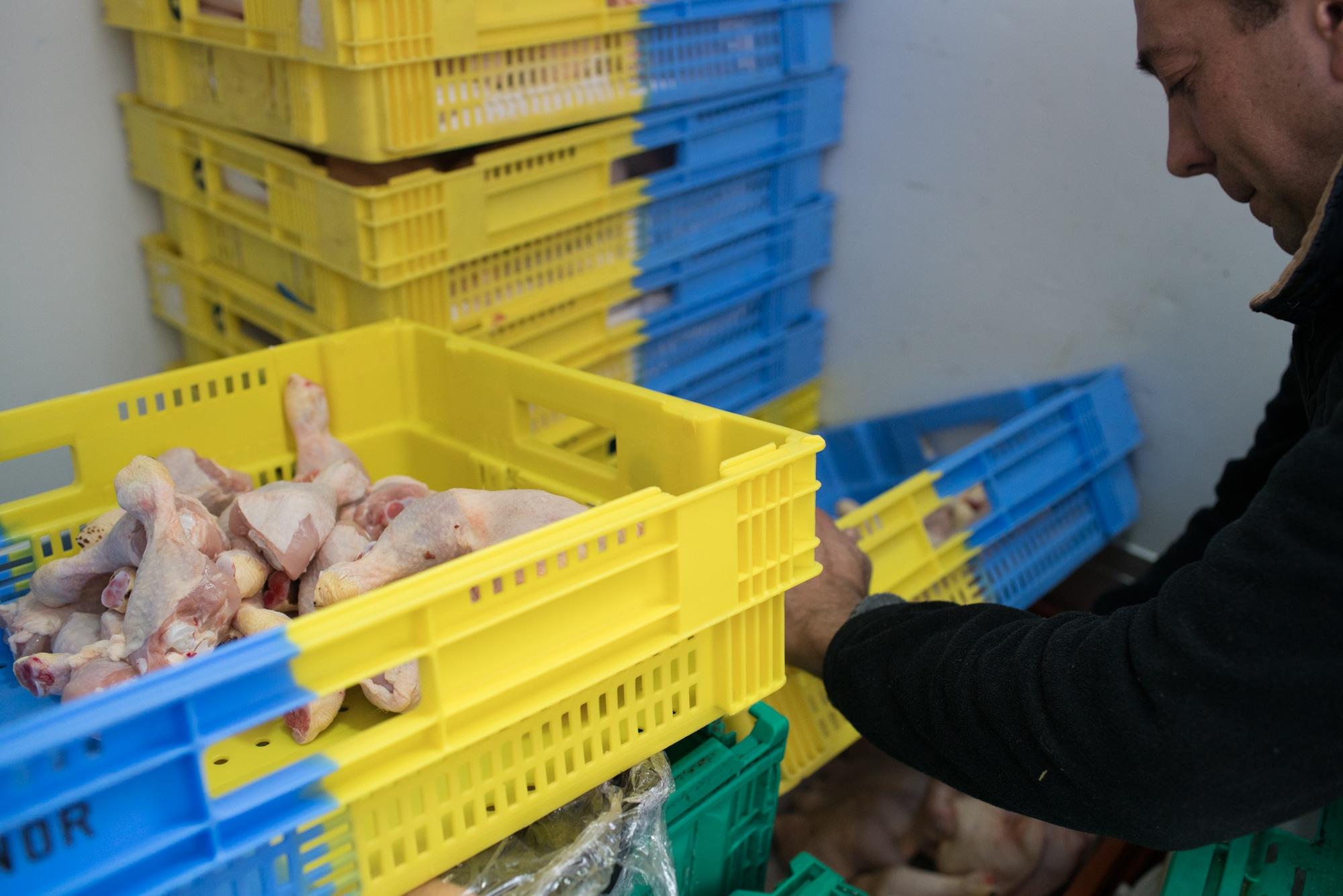Alain empile des caisses contenant de la volaille.