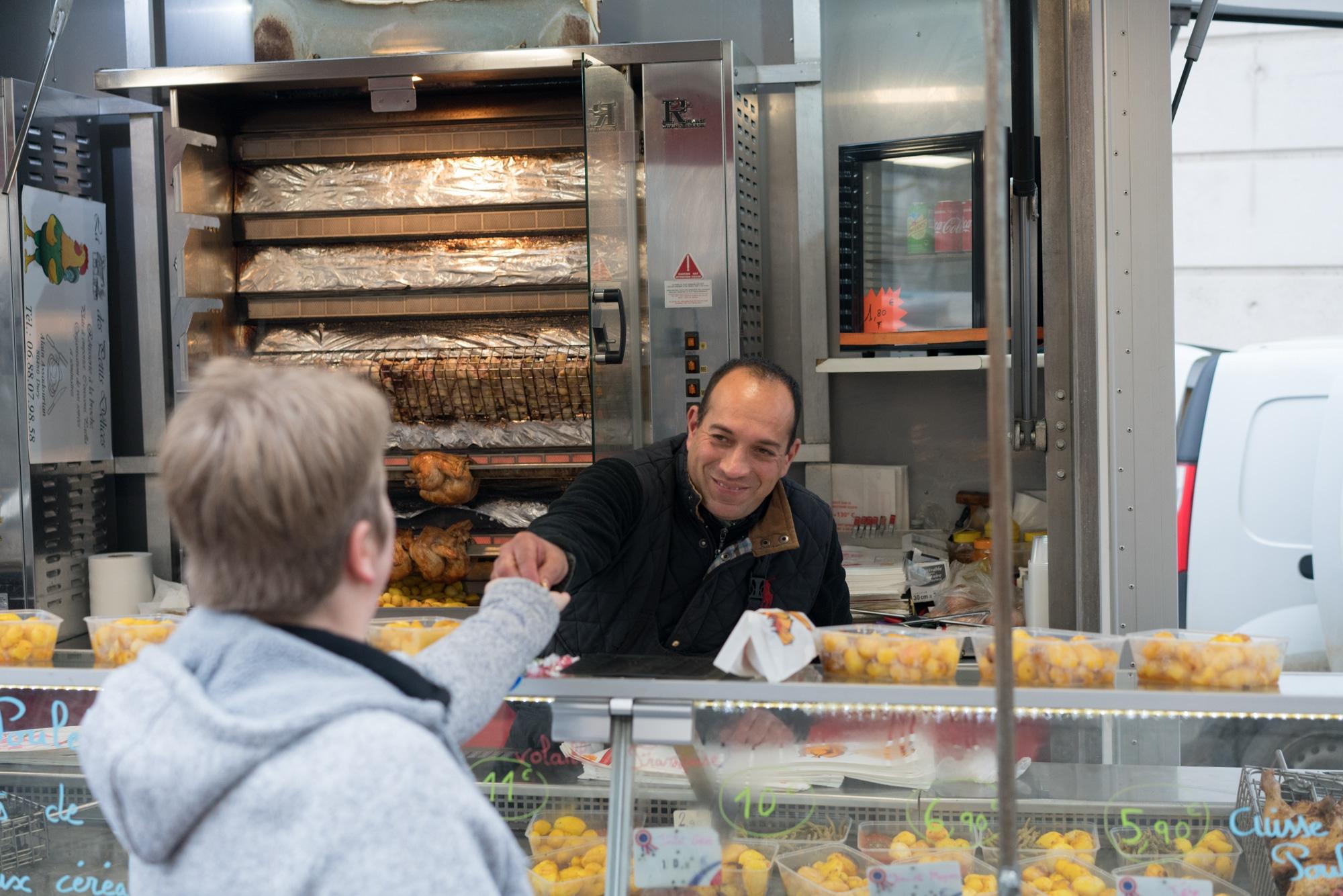 Alain, souriant, rend la monnaie à une cliente.