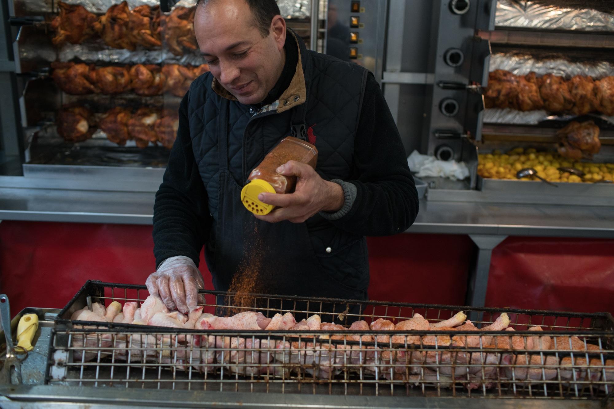 Alain verse des épices sur des parts de poulets rangés dans une grille.