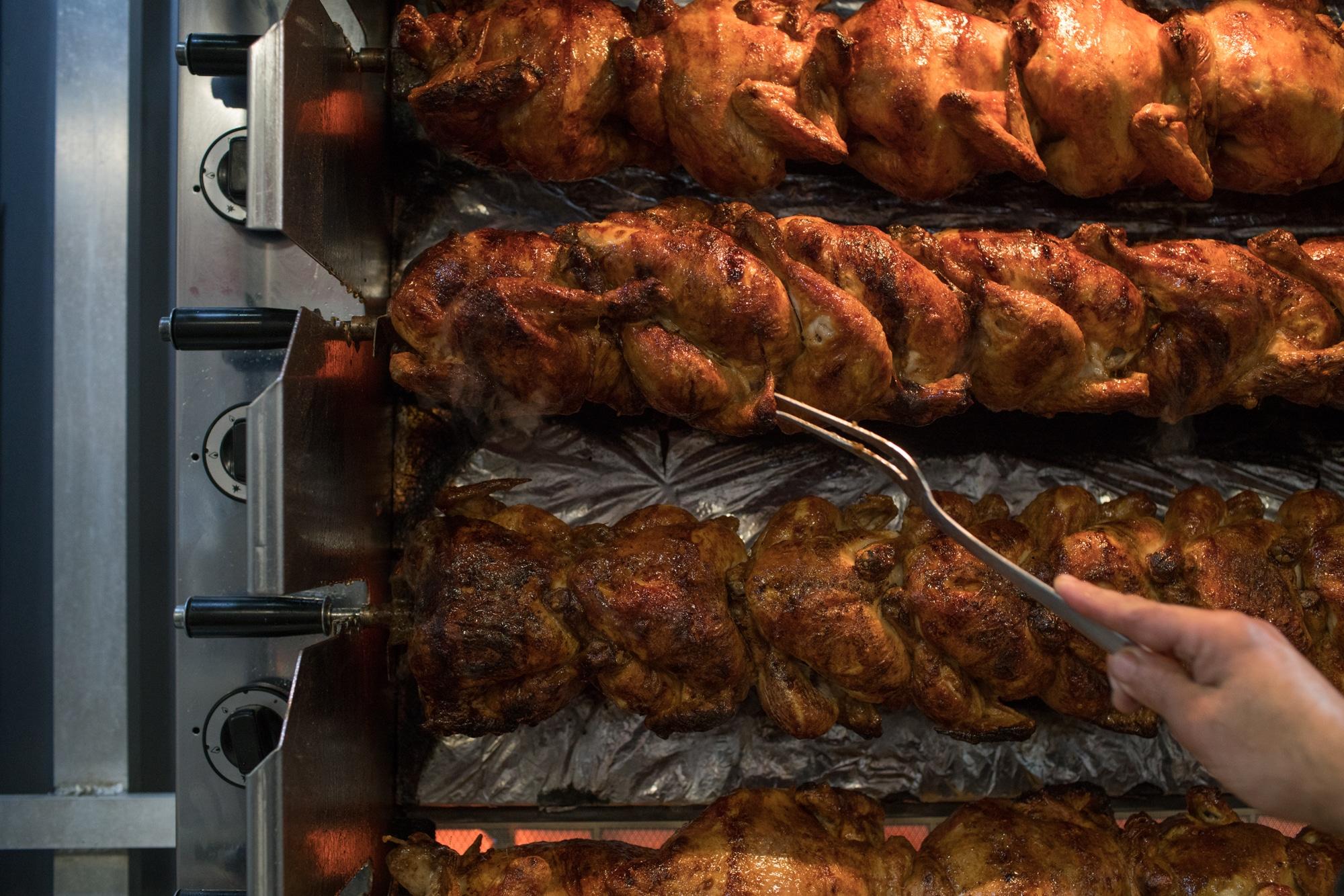 Alain vérifie la cuission des poulets à l'aide d'une longue fourchette.