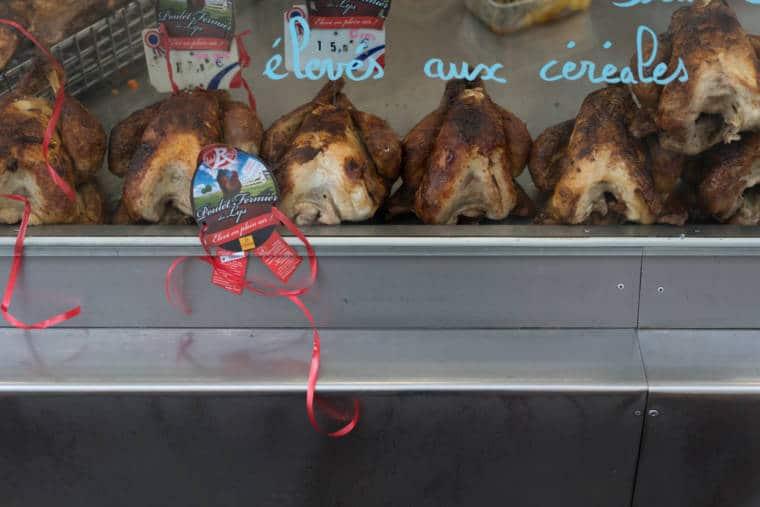 Des poulets rôtis sont présentés dans la vitrine du camion.