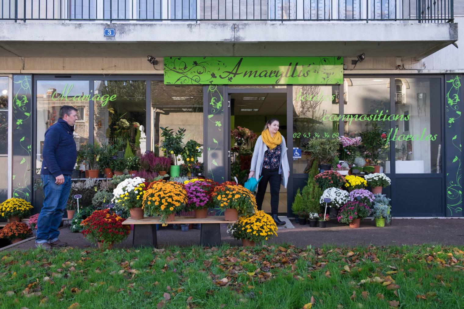 Aurélie sort de la boutique Amaryllis, un arrosoir à la main parmi les fleurs