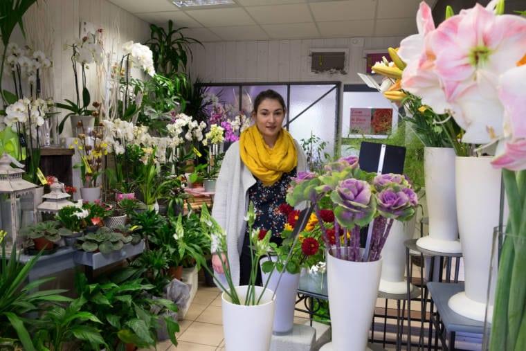 Aurélie se tient au milieu de la boutique, entourée de fleurs