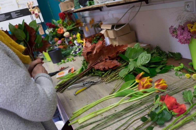 Détail du plan de travail permettant de couper les fleurs. Les mains d'Aurélie assemblent différents feuillages