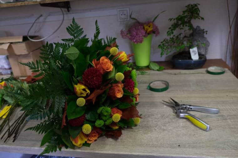 Un bouquet aux couleurs automnales est posé sur le plan de travail à côté d'un sécateur