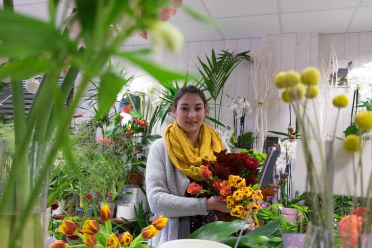 Aurélie se tient au milieu de sa boutique, tenant un assemblage de bouquets