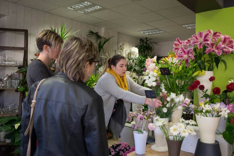 À la demande de clientes, Aurélie saisit des fleurs blanches pour constituer un bouquet