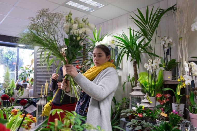 Aurélie, tenant dans sa main une ébauche de bouquet, assemble différentes espèces de fleurs