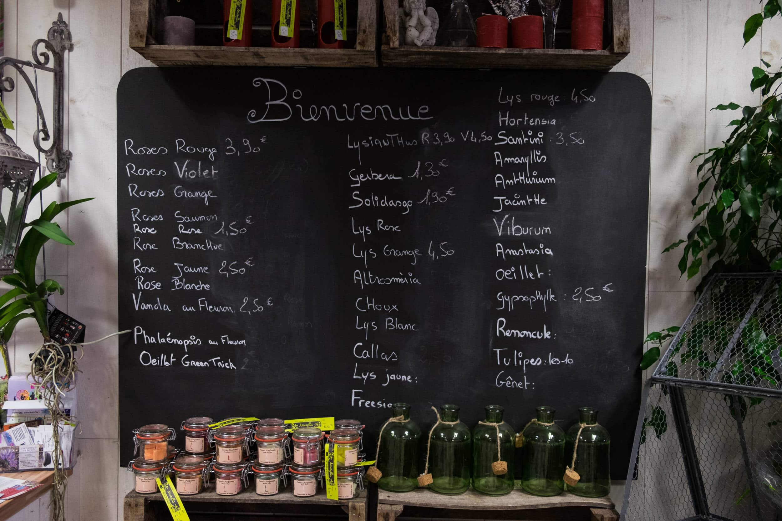 Un tableau noir présentant les tarifs de fleurs écrits à la craie blanche. Sous le tableau sont présentés des pots en verre