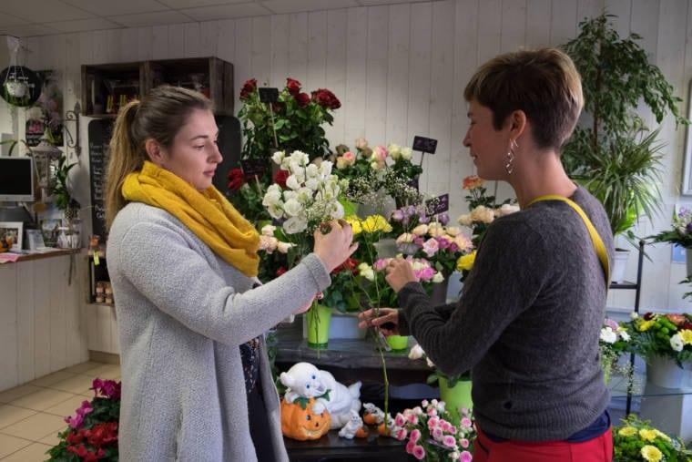 Aurélie et sa cliente, de part et d'autre d'un bouquet, le composent
