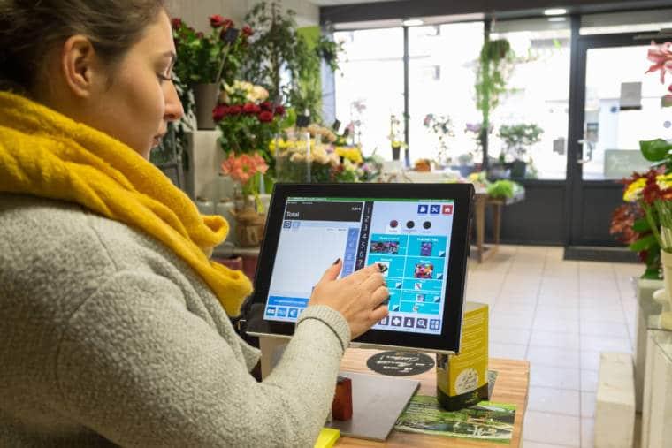 Aurélie montre le fonctionnement de sa caisse, un écran tactile contenant des informations détaillées sur les types de produits vendus