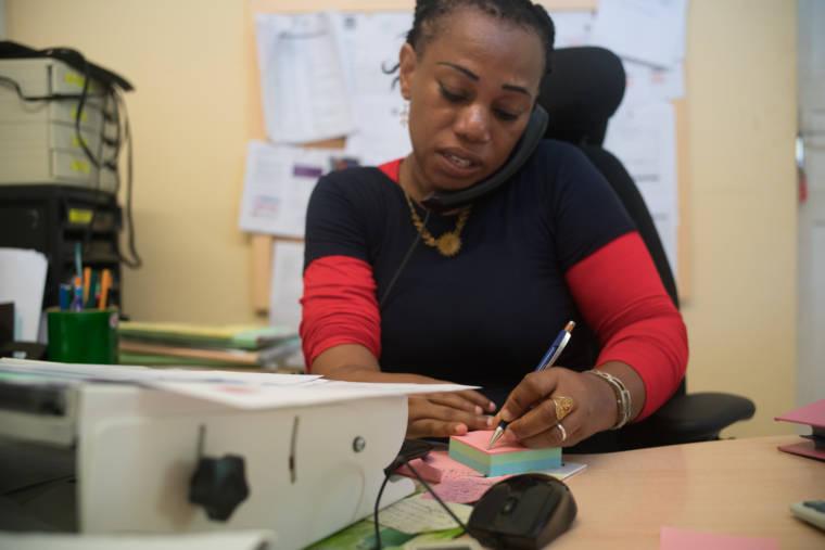 Hayati, au téléphone, prend des notes sur un post-it