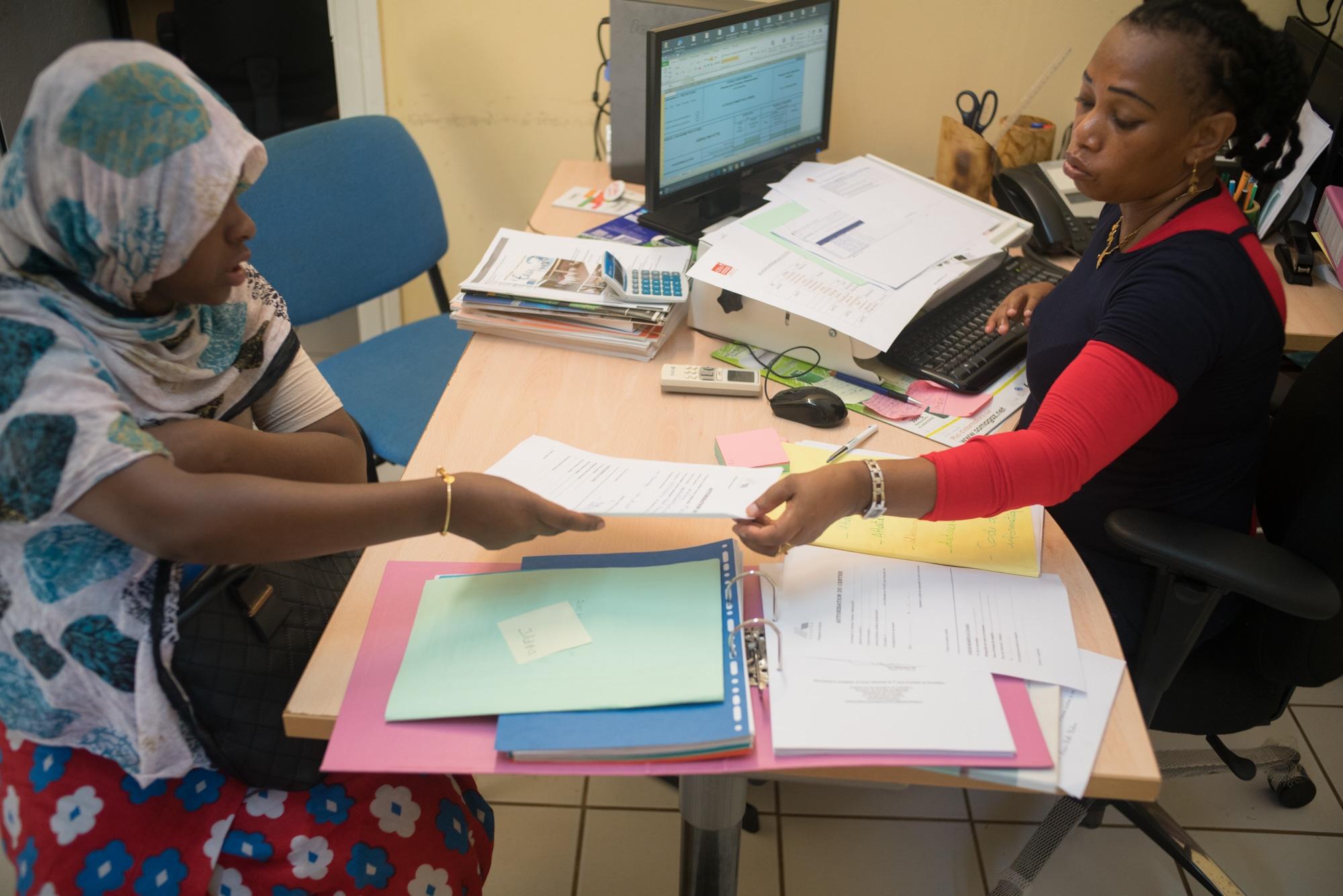 Hayati tend des documents imprimés à la personne qu'elle reçoit dans son bureau