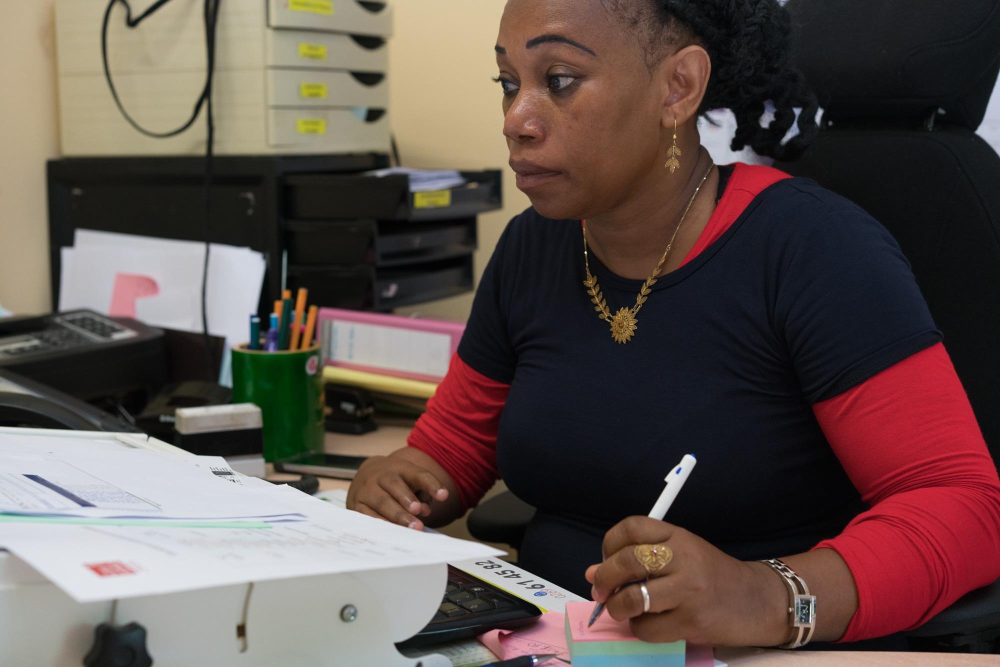 Hayati prend des notes sur un post-it. Devant elle on aperçoit un système pour surélever son poste de travail