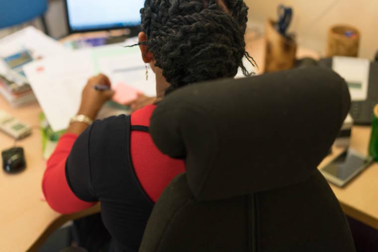 Hayati, assise à son bureau, est photographiée de dos. On aperçoit son siège ergonomique