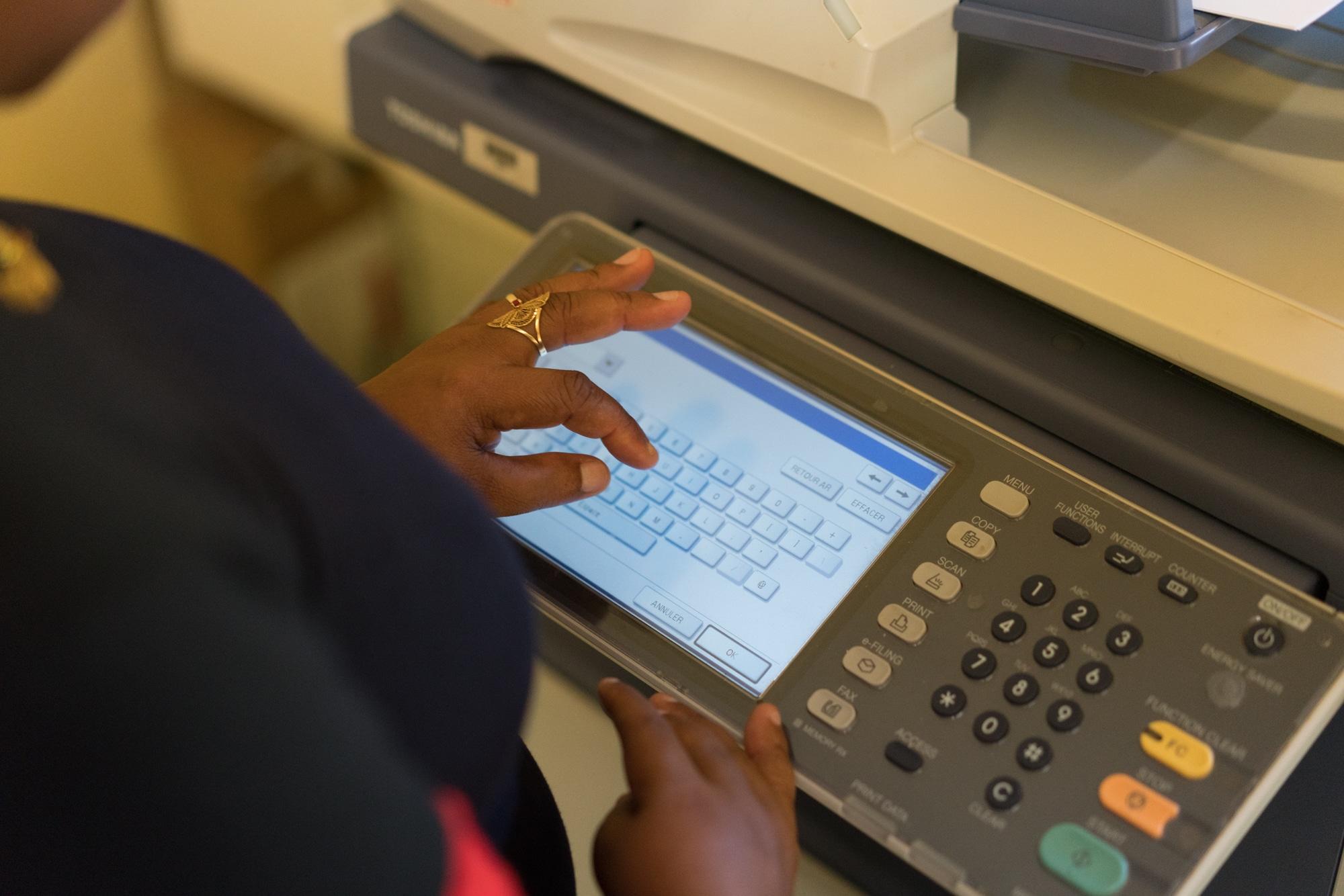 Les mains d'Hayati tapent une adresse email sur l'imprimante