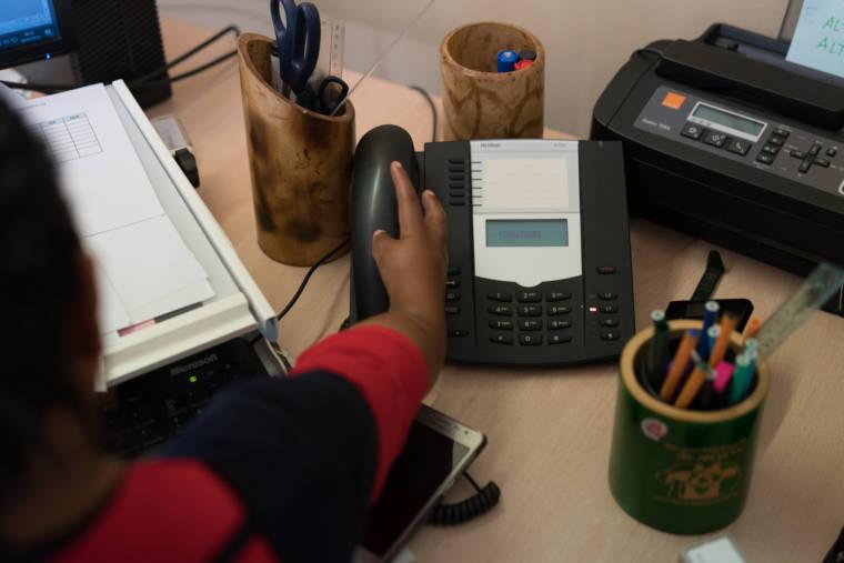 """La main d'Hayati saisit son téléphone fixe. Sur l'écran du téléphone on peut lire le mot """"Formateurs"""""""