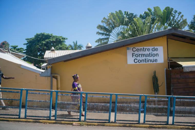 """En extérieur, on aperçoit le bâtiment dans lequel travaille Hayati. Au premier plan, sur le bâtiment, un écriteau signale """"Centre de formation continue"""". Au second plan, des arbres exotiques se découpent sur le ciel bleu"""