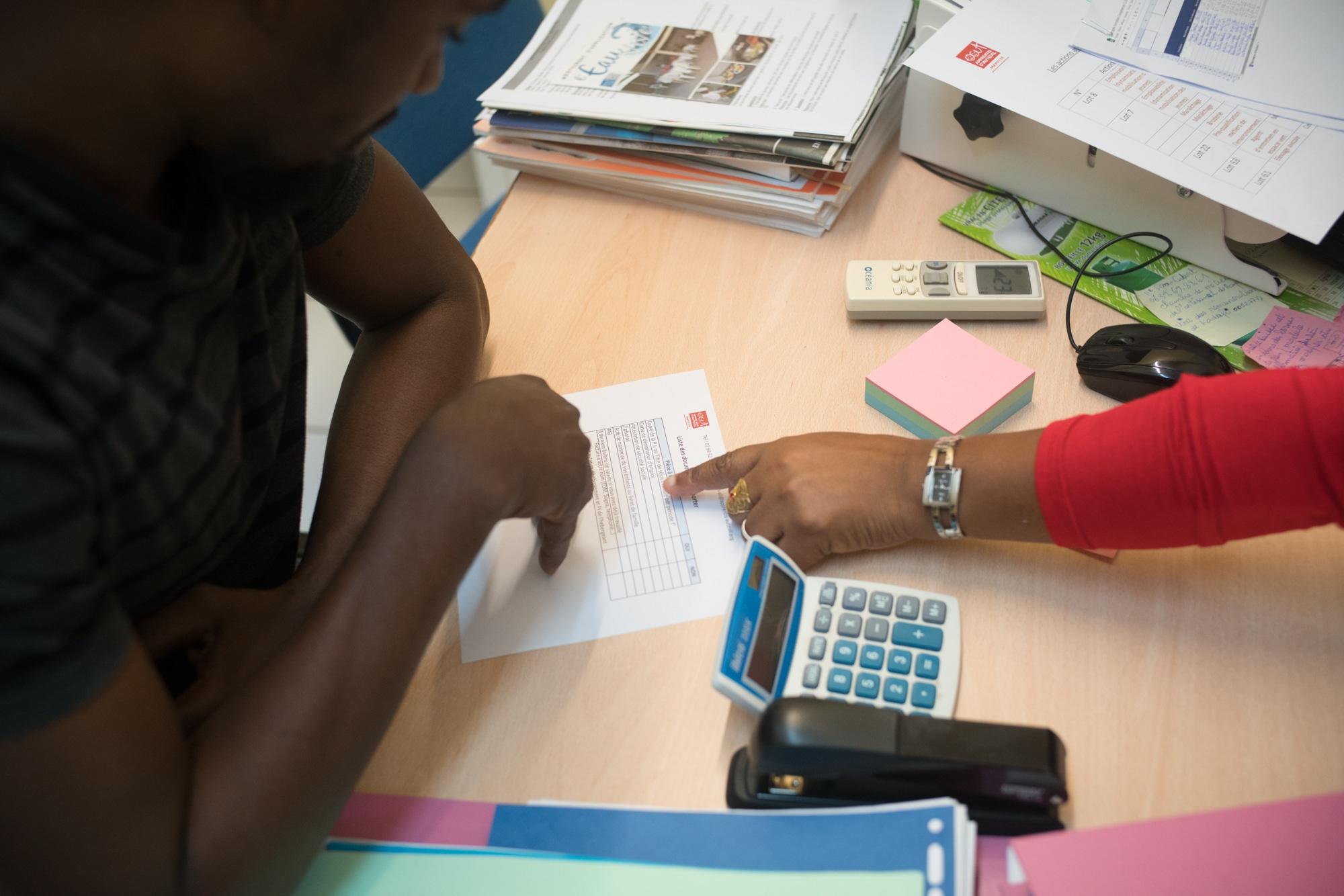 La main d'Hayati désigne une ligne d'un document imprimé à son interlocuteur