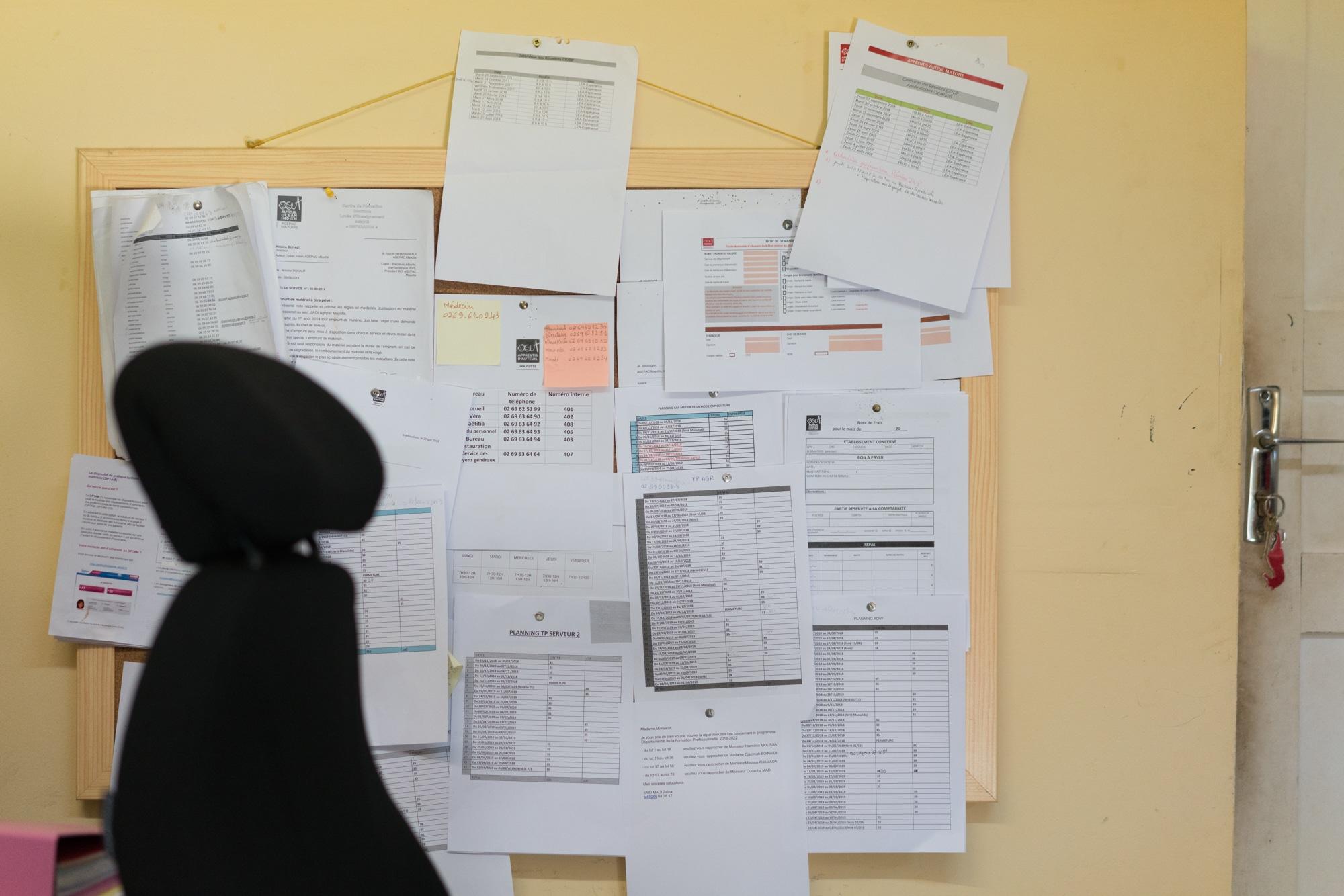 Un tableau d'affichage recouvert de documents imprimés est accroché dans le bureau d'Hayati