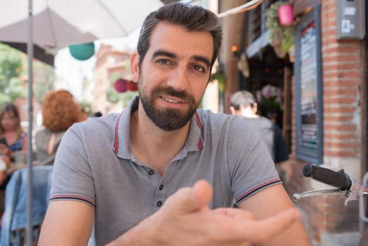 Christophe Debard, assis en terrasse, souriant