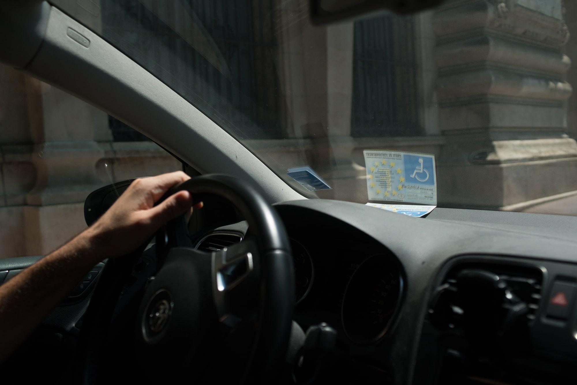La main de Christophe sur le volant de sa voiture. Dans le pare-brise se reflète sa carte de stationnement pour personne handicapée